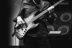 Bass guitar player on a stage near speakers Stock Photo