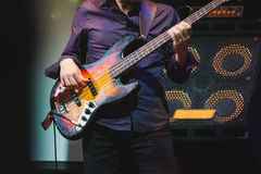 Bass guitar player on a stage near speakers Royalty Free Stock Images