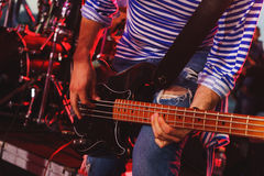 Bass guitar player on stage during a performance in yarih lights close up. Stock Photo