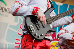 Bass guitar player in traditional Russian clothes. Close up musician playing bass guitar on a Russian fair festival Stock Photos