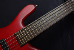 Bass guitar with red body Royalty Free Stock Photography