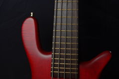 Red bass guitar. Bass guitar with red body on black Stock Images