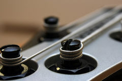 Bass guitar splittings. Close with the tense strings of silvery colour Stock Photos