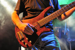 Bass Guitar on Stage. Close up of an electric bass guitar (5 string) being played on stage. Smoke and a drum-kit can be seen in the background royalty free stock photo