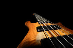 Bass guitar strings. With wooden close up black background Royalty Free Stock Photo