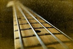 Bass guitar texture in the rain. Bass guitar theme with rain and showers sepia tone Royalty Free Stock Photography