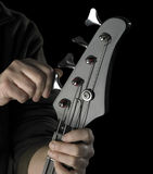 Bass guitar tuning. Detail of a black bass guitar while gets tuned in dark back Stock Photos