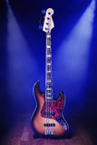 Bass Guitar on a  Wooden Stage. An Electric Bass Guitar Stood Upright on a Stand on a Wooden Stage Stock Photography