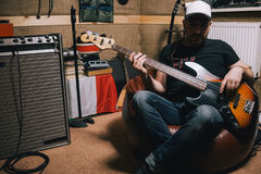Bass guitarist with guitar in garage studio stock image