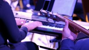 Bass guitarist and pianist. Closeup male hand holds the strings of a five-stringed guitar against the background of female hands w. Bass guitarist and pianist stock video footage