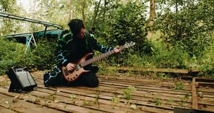 The bass guitarist plays on his knees on the old wooden pier. stock video footage