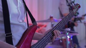 The bass guitarist pushes the strings close-up. Playing the bass guitar. stock video footage