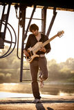 Bass guitarist at sunset. Young man play bass guitar at industrial area by the river at sunset, full body shot royalty free stock photos
