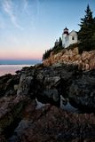 Bass Harbor. The Bass harbor light in Maine is a stunning setting, with the Light resting on a cliff. The water rests in the rocky shoreline at low tide causing stock images