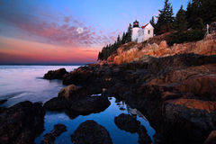 Bass Harbor Lighthouse at Dawn. Bass Harbor Lighthouse in Acadia National Park, Maine.  A lighthouse atop a rocky cliff set against the dawn sky and calm ocean Royalty Free Stock Photo