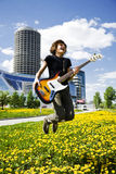 Bass player. Young bass player jumping in the city Royalty Free Stock Photography