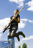 Bass player. Young bass player jumping in the city Stock Images