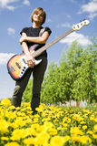 Bass player. Young bass player in the field Royalty Free Stock Images
