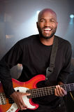 Bass player. Laughing bass guitar player in a club setting Royalty Free Stock Image
