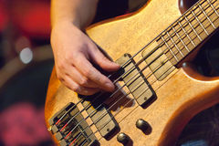 Bass player. Hand of bass player while playing bass, colorful background Royalty Free Stock Images