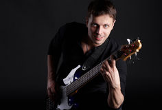 Bass player. The smiling man with bass guitar in hands Stock Photography
