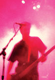 Bass player atmosphere. Grainy blurry atmospheric abstract image of a bass player in front of a microphone.  Shot with 3200 iso slide film Stock Photo