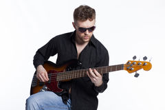 Bass player with attitude. Playing guitar gently in love with music Royalty Free Stock Photos
