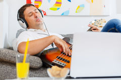 Bass player. Enjoying and playing in the living room Stock Images
