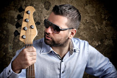 Bass player with glasses. Against grungy background Royalty Free Stock Photography
