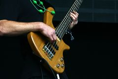 Bass player hands with five string bass guitar. Natural finish. Green necklace made of green thread is visible royalty free stock images