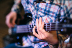 Bass player holding guitar neck focus Royalty Free Stock Image