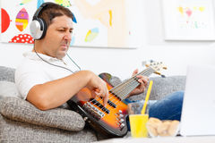 Bass player. Man improving hiss playing abilities with his bass guitar at home Royalty Free Stock Images
