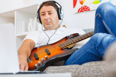 Bass player. Playing to a track in the living room Royalty Free Stock Image