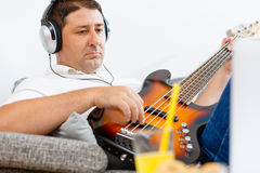 Bass player. Practicing and having a drink in his living room Royalty Free Stock Photos