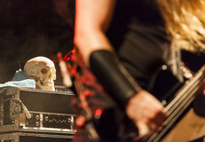 Bass player at a rock concert. With a skull in the background Royalty Free Stock Photo