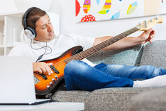 Bass player. Tuning his guitar in the living rom Royalty Free Stock Image