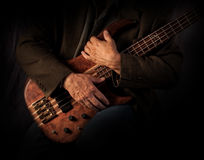 Bass Players Hands. A musician caressing his electric bass guitar stock image