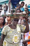 Old woman charging statutes. Bassam ,  Côte d`Ivoire – November  7 ,  2015 :  Wants woman in black glasses and scarf on her head, loads a tray containing Stock Photos