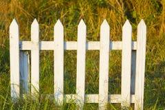 Basse petite barrière en bois blanche dans l'herbe Photographie stock libre de droits