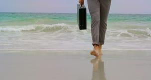 Basse section d'homme d'affaires marchant nu-pieds avec la serviette sur la plage 4k banque de vidéos