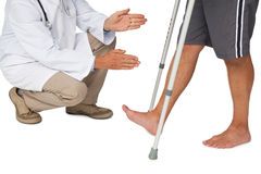 Basse section d'un docteur avec l'homme supérieur employant le marcheur Photo stock