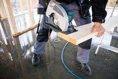Basse section de charpentier Using Electric Saw pour couper le bois Photographie stock