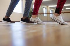 Basse section de femme avec l'ami préparant la danse sur le plancher Images stock