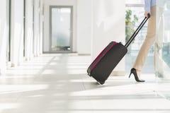 Basse section de femme d'affaires avec le bagage quittant l'aéroport Photographie stock libre de droits