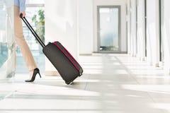 Basse section de femme d'affaires avec le bagage quittant l'aéroport Photos libres de droits