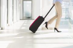 Basse section de femme d'affaires avec le bagage sortant l'aéroport Photos stock