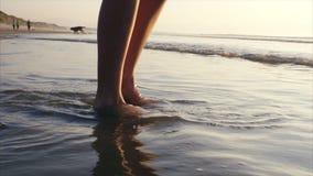 Basse section de femme jouant avec des vagues se cassant sur le rivage banque de vidéos