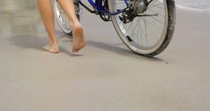 Basse section de femme marchant avec une bicyclette sur la plage 4k banque de vidéos