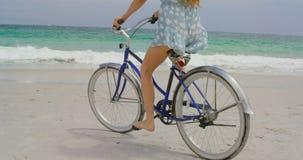 Basse section de femme montant une bicyclette sur la plage 4k banque de vidéos