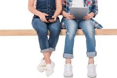 Basse section de garçon et de fille à l'aide des dispositifs numériques tout en se reposant sur le banc Image stock